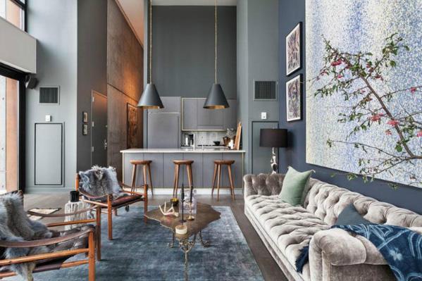 Szaro niebieski salon z otwartą kuchnią i kanapą glamour