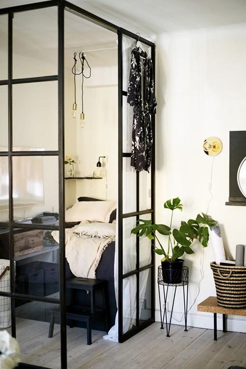 Sypialnia wydzielona za pomocą szklanych drzwi ze szprosami