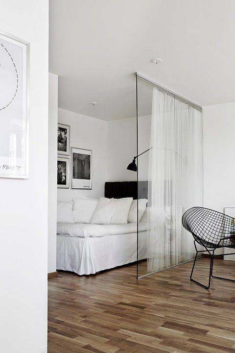 Sypialnia wydzielona z salonu za pomocą gładkiej tafli szkła