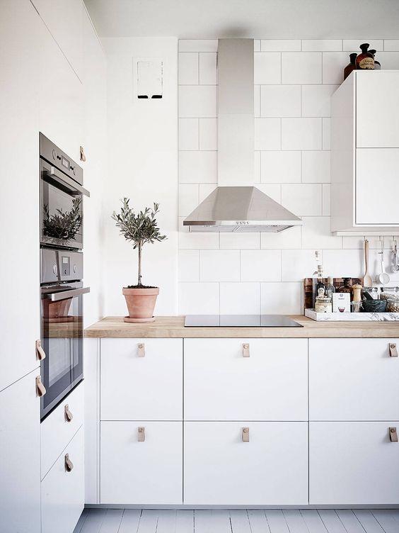Białe szafki kuchenne z chromowanym okapem