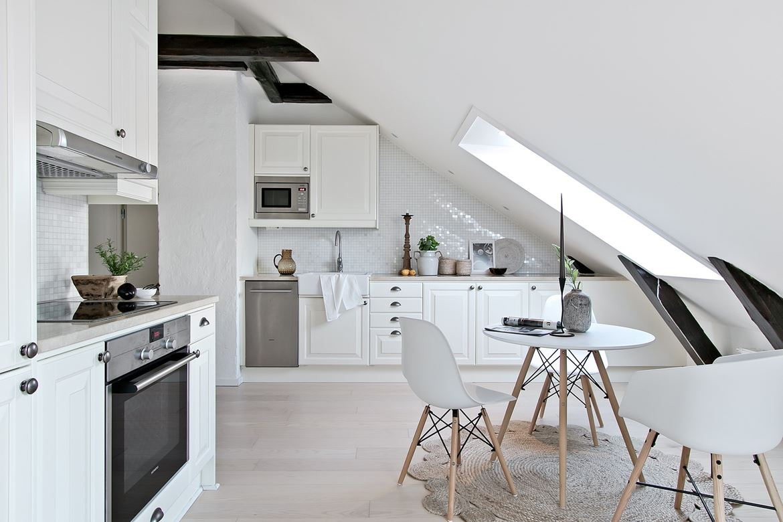 Biała kuchnia z drewnianymi belkami stropowymi