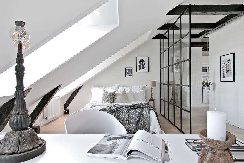 Sypialnia na poddaszu z drewnianymi belkami stropowymi