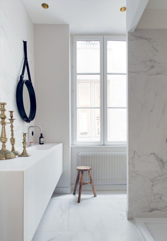 Biała marmurowa łazienka ze złotymi świecznikami