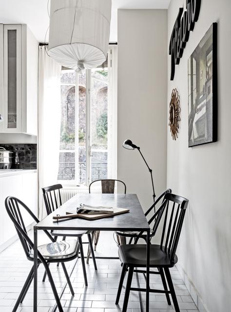Biała kuchnia z czarnym stołem i krzesłami