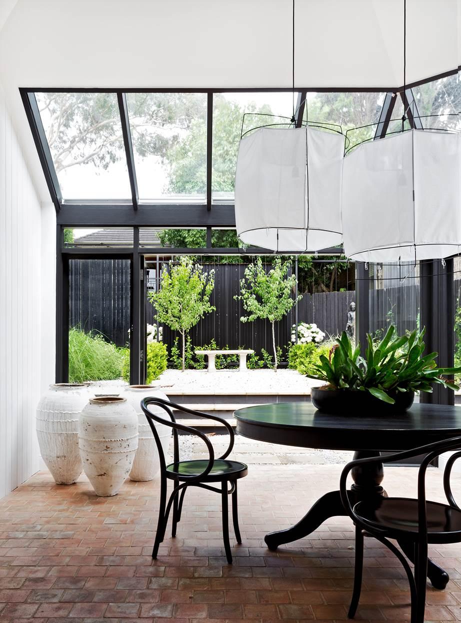 Atrium w domu z dużymi oknami w czarnej ramie