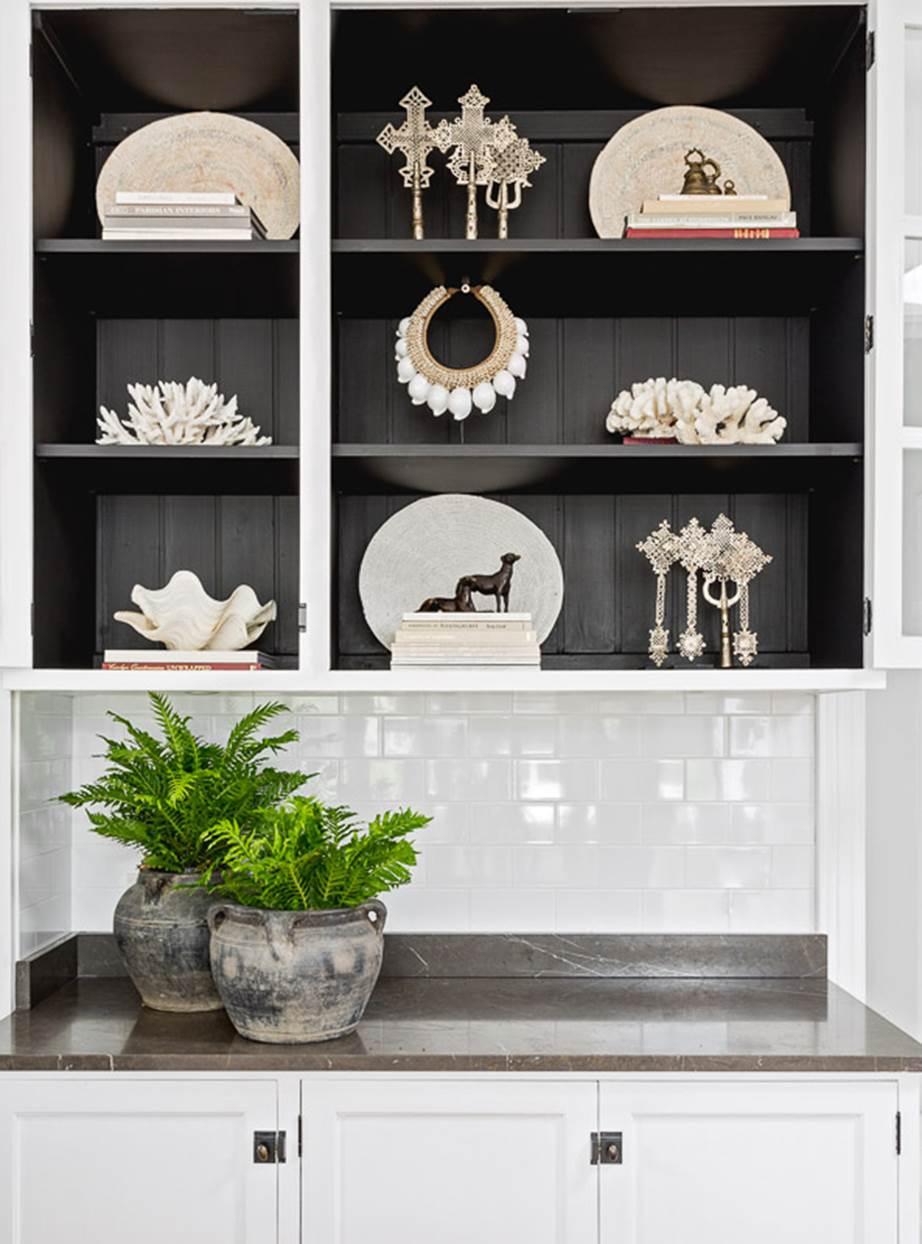 Czarne półki w kuchni z białymi dekoracjami