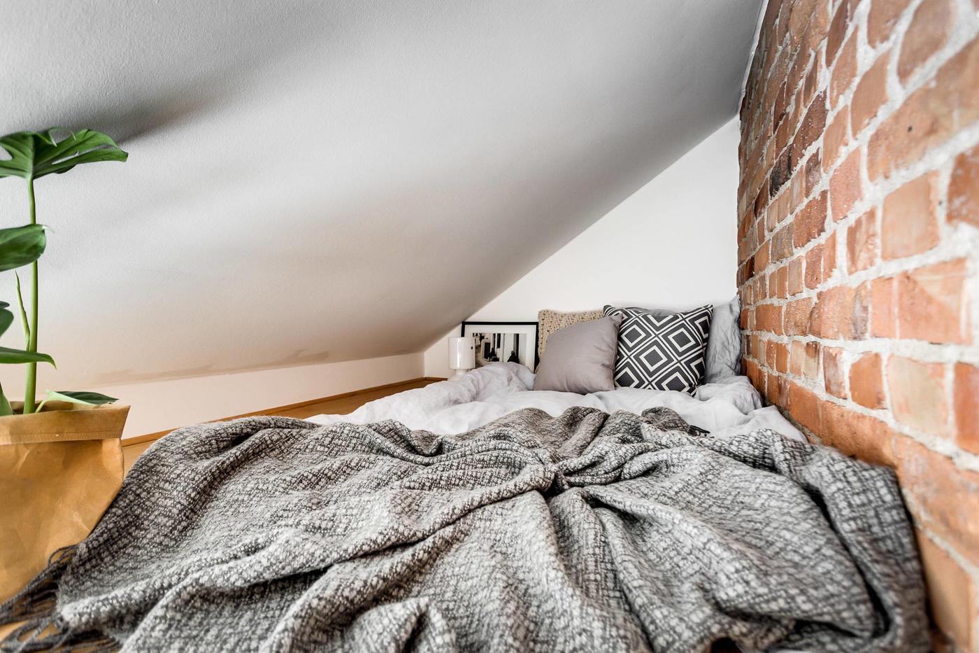Sypialnia na antresoli z cegłą na ścianie