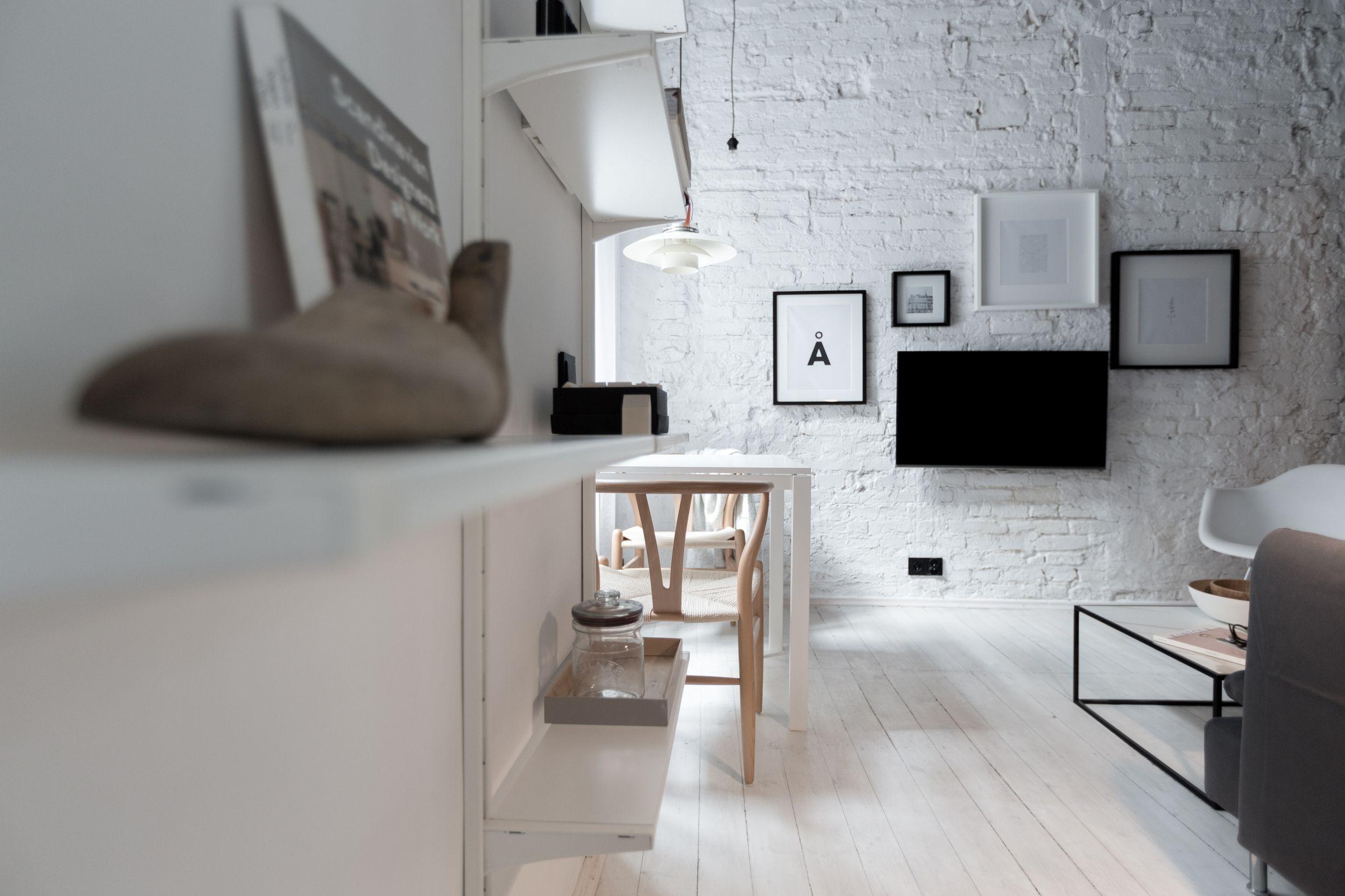 Biała cegła na ścianie w salonie z galerią ścienną