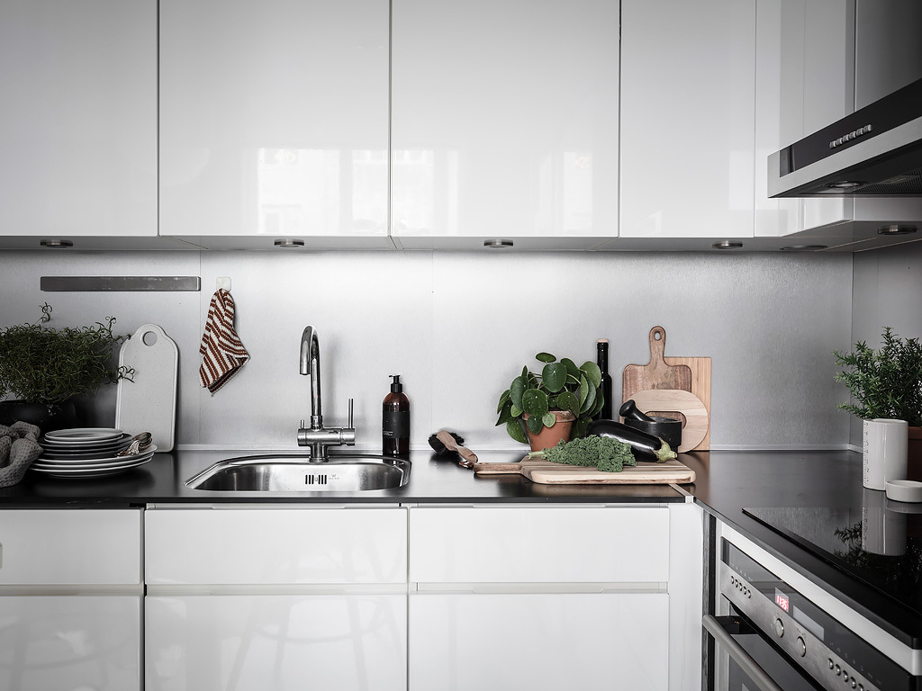 Biała nowoczesna zabudowa kuchenna w tylu skandynawskim