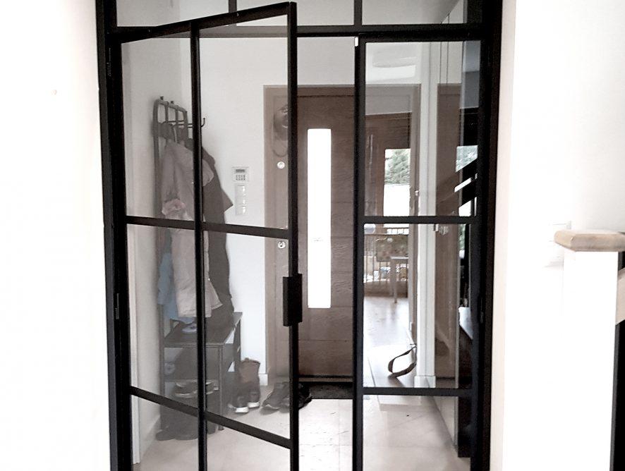 Szklana ściana z czarnymi szprosami na korytarzu
