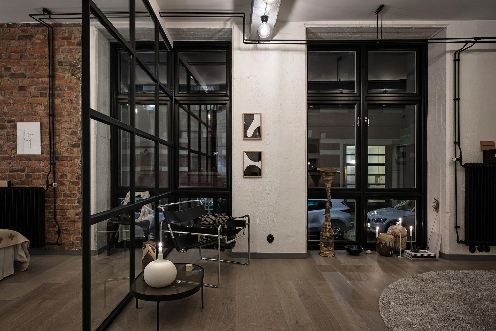 Salon ze szklaną ścianą z czarnymi szprosami