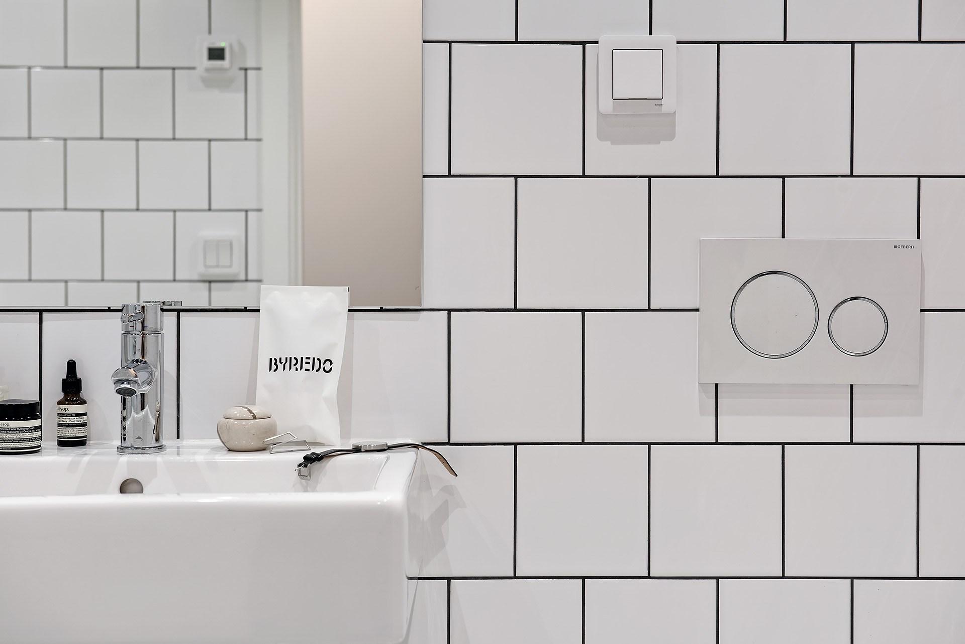 Białe kafle w łazience z czarną fugą