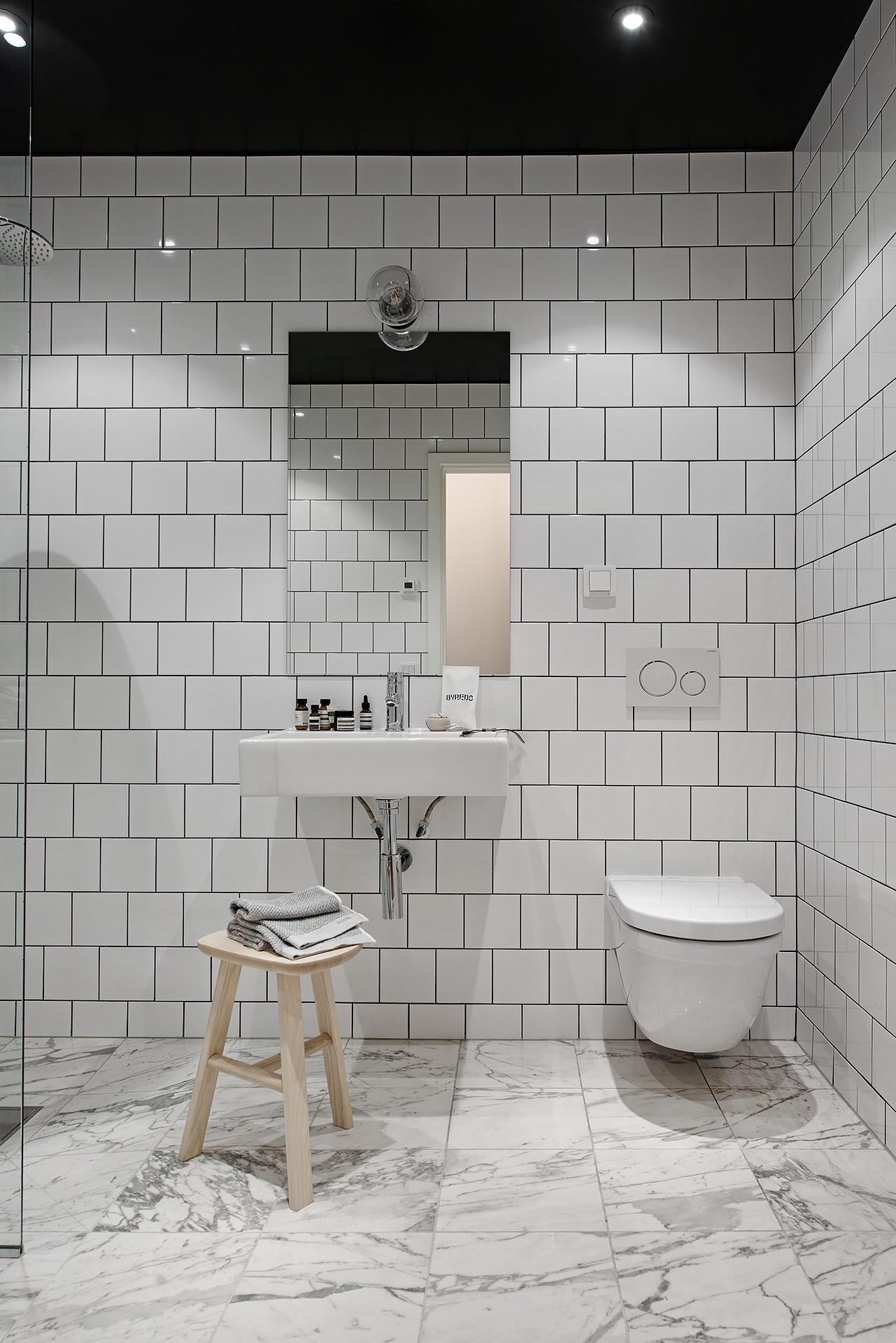 Łazienka z czarnym sufitem i marmurową podłogą