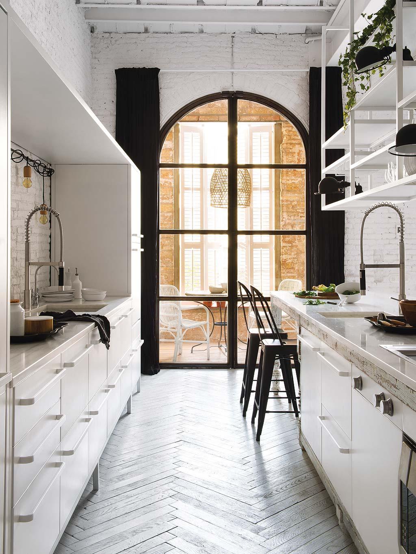 Biała kuchnia z cegłą i wyspą kuchenną