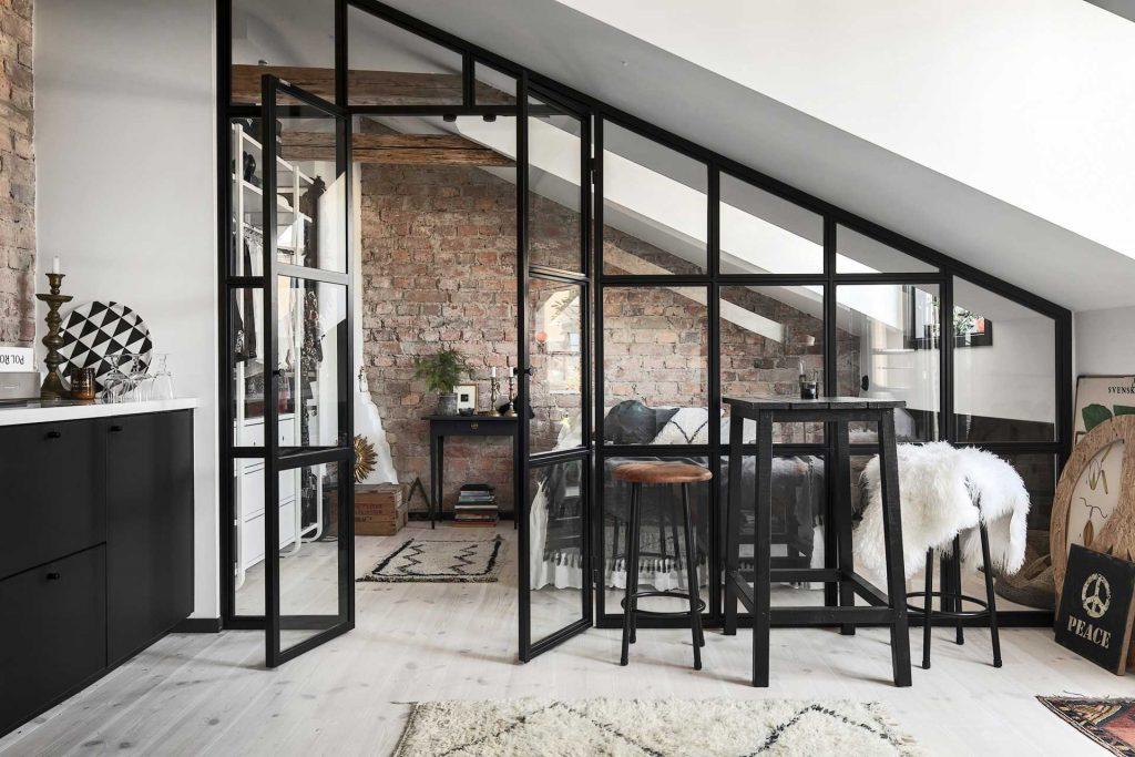 Sypialnia ze szklaną ścianą działową i starą cegłą