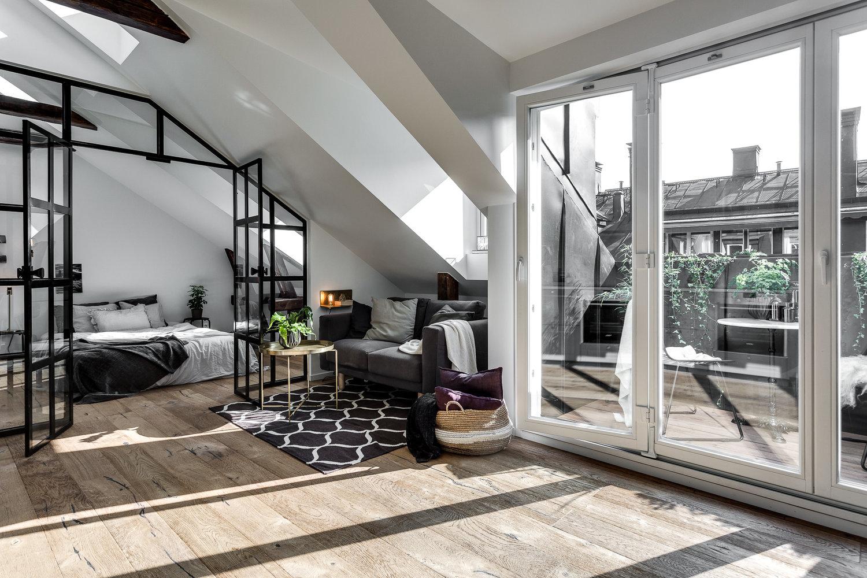 Skandynawski salon na poddaszu ze skosami i balkonem