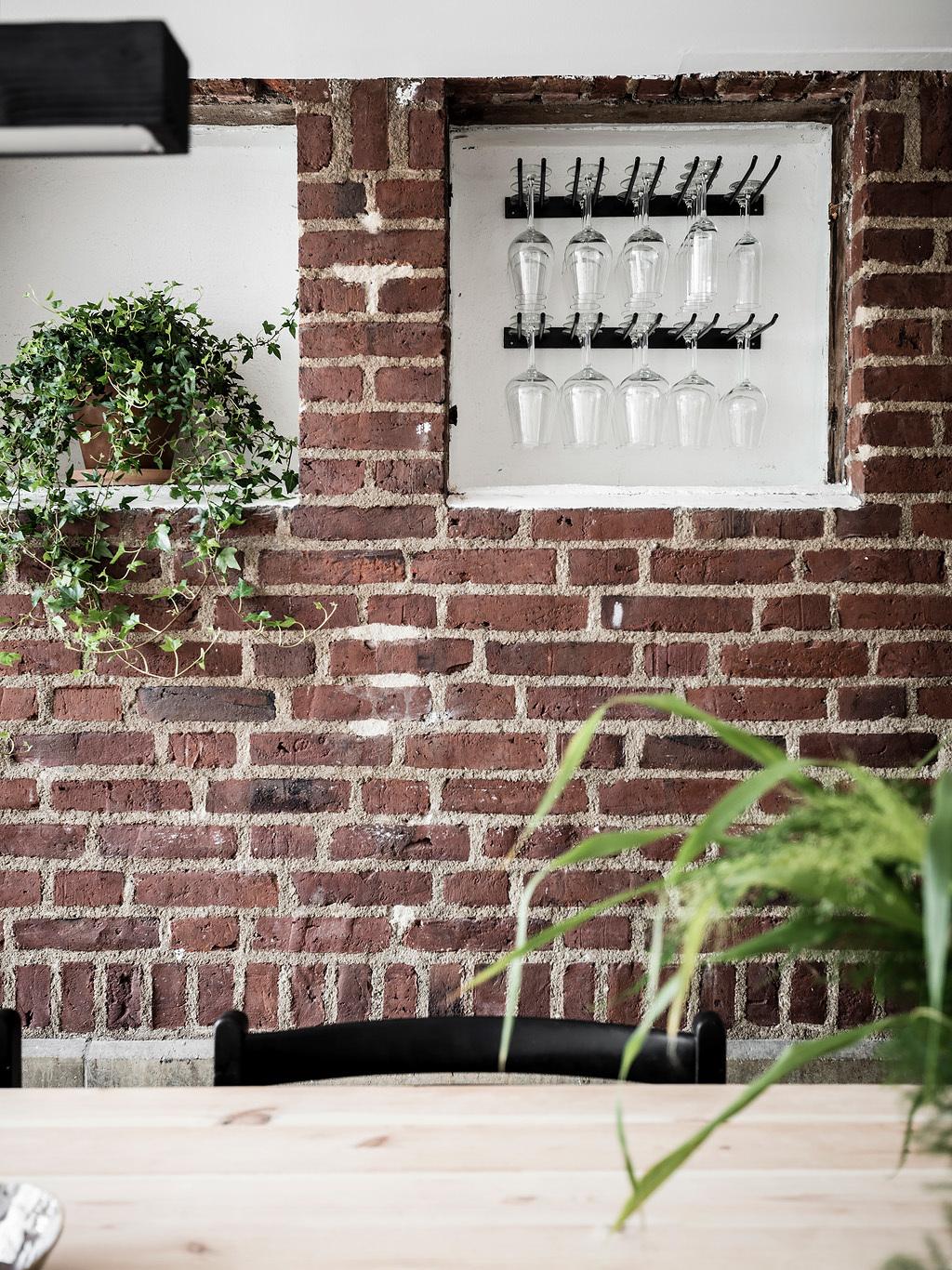 Cegła na ścianie w kuchni z wiszącymi kieliszkami
