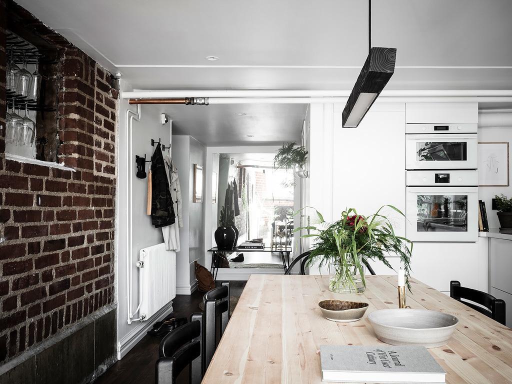 Skandynawska kuchnia z cegłą na ścianie