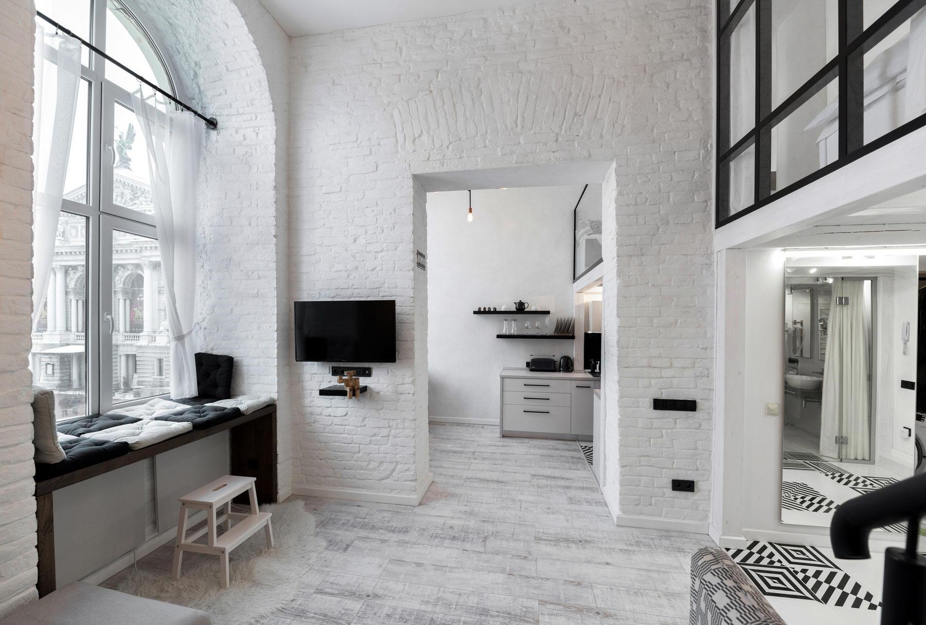 Salon z bieloną cegłą i czarnymi dodatkami