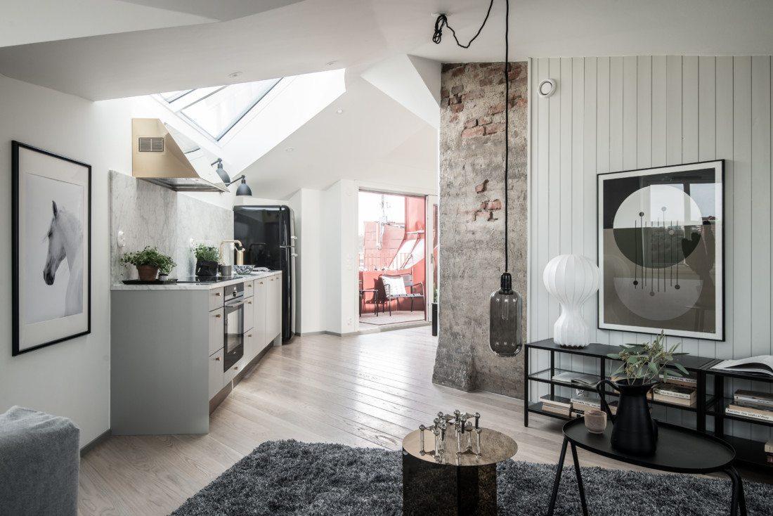Salon z kuchnią w mieszkaniu ze skosami