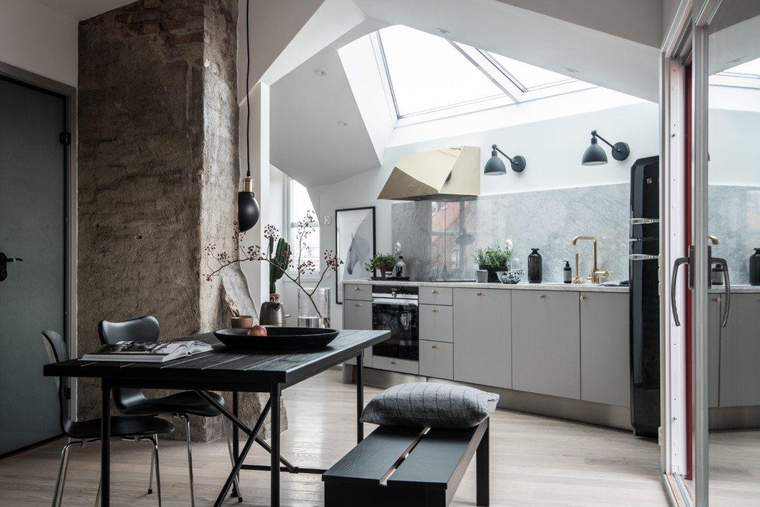 Małe mieszkanie ze skosami, oknami w suficie i ceglaną ścianą