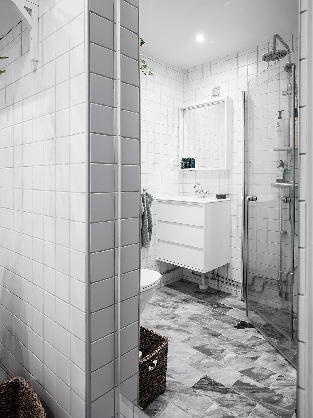Biała łazienka z szarymi kaflami na podłodze