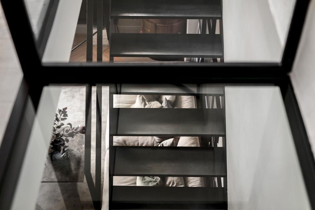 Dwupiętrowe mieszkanie z czarnymi schodami