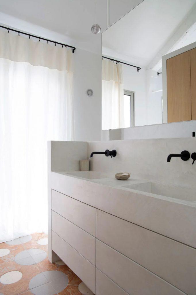 Biała łazienka z czarną armaturą i terrakotą na podłodze